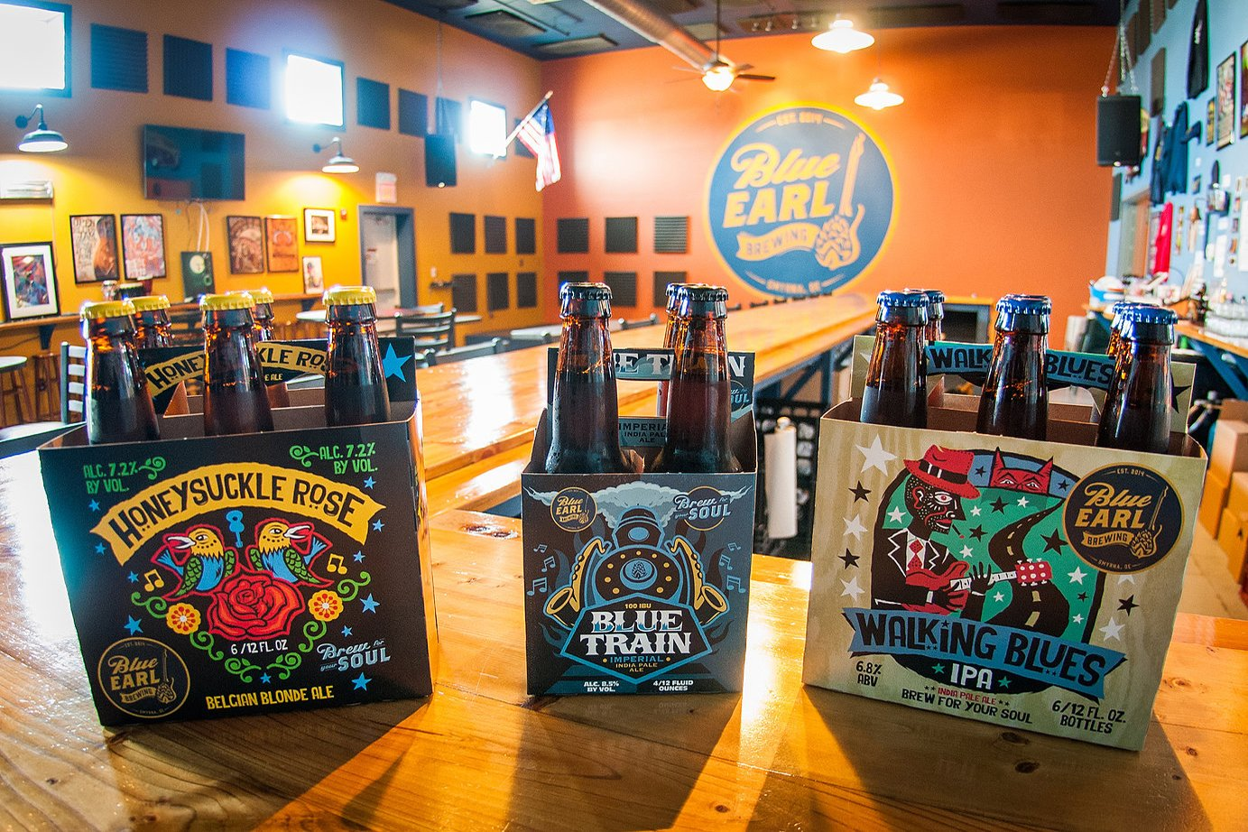 Some of Blue Earl's package goods. A 4 pack of Blue Train, a 6 pack of Honeysuckle Rose, as well as Walking Blues IPA.